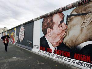 """Eine Passanten betrachtet am Freitag (06.11.2009) an der frisch restaurierten East Side Gallery in Berlin das Gemälde """"Bruderkuss zwischen Honecker und Breschnew"""" von Dimitrij Vrubel. Grund für den Erfolg der Gallery seien die unterschiedlichen und internationalen Sichtweisen der Künstler auf den Mauerfall vor 20 Jahren. Monatelang war die im Lauf der Jahre blass gewordene Open-Air-Galerie restauriert worden. 94 der 118 Künstler, die im Jahr nach dem Mauerfall 1990 ihre Bilder an die Mauer gemalt hatten, kamen dafür wieder nach Berlin. Foto: Wolfgang Kumm dpa/lbn +++(c) dpa - Bildfunk+++"""